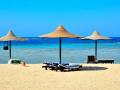 spiaggia di sabbia e  ombrelloni di paglia